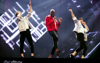 Boris René performing with two male dancers